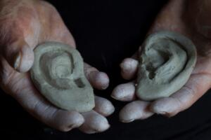view Human head sculpted in clay, hands holding clay ears