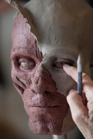 view Human head sculpted in clay, completing the eye