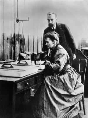 view Pierre and Marie Curie at work in their laboratory.