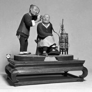 view Model of Chinese barber cleaning ears of client.