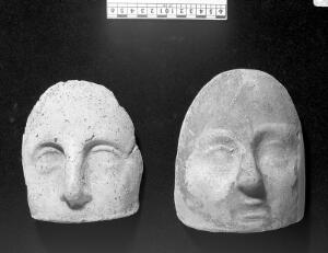 view Votive offerings in the form of the face. Apparently terracotta.