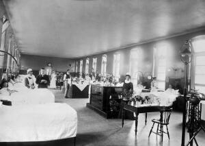 view Royal Portsmouth Hospital: Victoria Ward, with women patients, members of the medical staff and nurses. Photograph, 1902.
