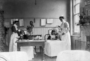 view Part of a children's ward in a hospital with two nurses attending two children. Photograph.