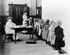 view Women sanitary inspector examining young girls hair