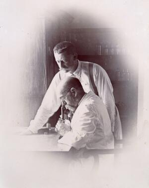 view Robert Koch and Richard Pfeiffer working in a laboratory, investigating the plague in Bombay. Photograph attributed to Captain C. Moss, 1897.
