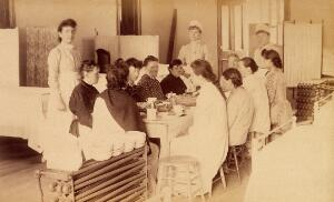 view Bellevue Hospital, New York City: women patients (mentally ill?) having a meal in a ward, with three nurses. Photograph.