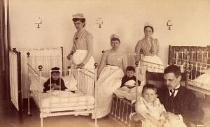 view Bellevue Hospital, New York City: children in a ward with nurses and a doctor (?). Photograph.
