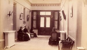 view Bellevue Hospital, New York City: a corridor inside entrance to building, with seated women (patients?). Photograph.
