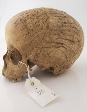 view Human skull inscribed with prayers for the deceased. Collected by Robert Baden Powell's Asante (Ghana) expedition 1895