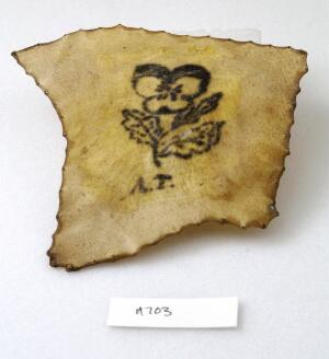 view A tattoo on a piece of human skin showing a flower and some initials