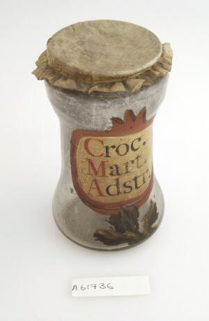 view Apothecary jar for iron oxide with painted label and parchment cover.