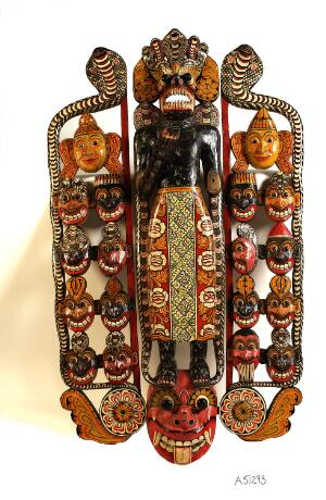 view Sinhalese mask used in exorcism and showing the heads of eighteen disease-spreading demons on either side of the central figure.