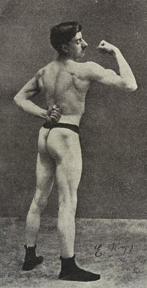 view Bodybuilder Emile Royer in bicep-curling pose