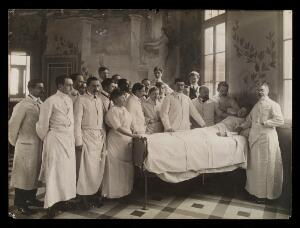 view Medical staff standing round a woman patient in bed in a hospital ward. Photograph by Seeberger Frères, ca. 1910.