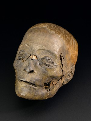 view Mummified head, without wrappings, no provenance, Egyptian, 2000-100 BC. Front 3/4 view of whole object on black background