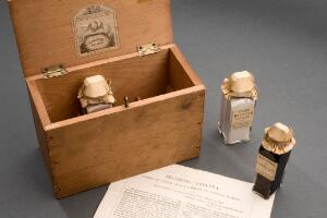 view Medicine chest, for cholera, after 1849, English. Chest open, bottles arranged outside of it. Grey background.