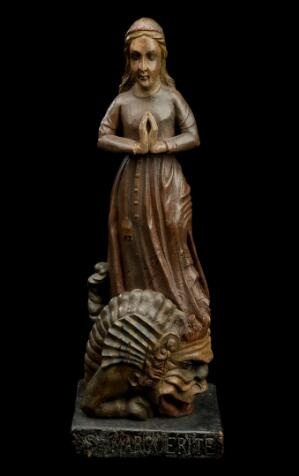 view Wooden statue of Saint Margaret of Antioch, patron of nurses, invoked by married woman and against sterility, wounds and facial blemishes, possibly French, 1700-1850. Full view, black background.