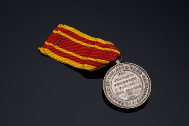 Hong Kong Plague Medal 1894, silver medal with silk ribbon, awarded to Private S. Abbey of Shropshire Light Infantry, by the Hong Kong Community for his services during the plague epidemic, by Bowcher and Wyon, English, 1894. Full view, reverse side on black perspex background.