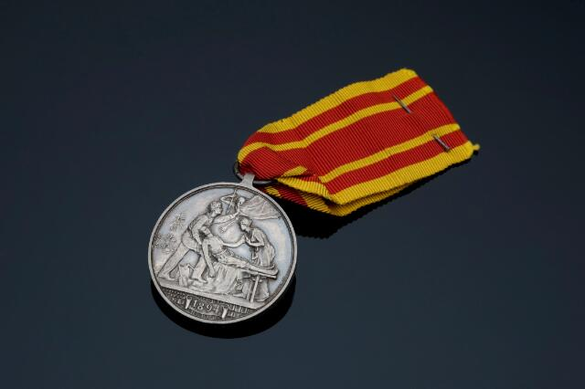 Hong Kong Plague Medal 1894, silver medal with silk ribbon, awarded to Private S. Abbey of Shropshire Light Infantry, by the Hong Kong Community for his services during the plague epidemic, by Bowcher and Wyon, English, 1894. Full view, showing front face, black perspex background.