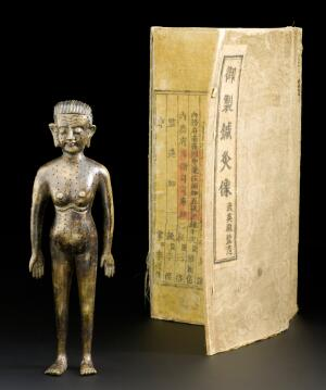 view Bronze acupuncture figure, in silk covered box bearing text of an Imperial decree of Yung Chen, chinese, early 18th century Detail shot of top half of object. Front view of whole object on grey background