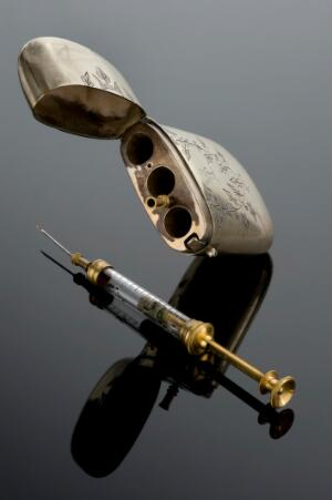 view Hypodermic syringe with spare needle and decorated metal cas