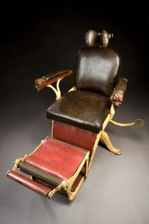 view Dental chair with hydraulic adjustment, c.1900. Full 3/4 view, graduated grey background.