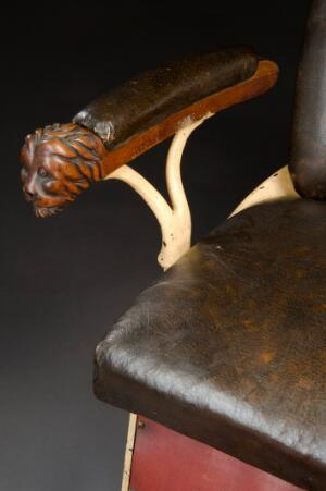 view Dental chair with hydraulic adjustment, c.1900. Detail of carved arm, graduated grey background.