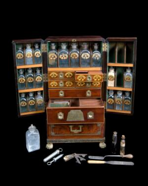 view Medicine chest, winged front, from Reece's Medical Hall, Piccadilly, with 30 painted glass bottles and 4 drawers, 5 confection glasses, 1 probang, 3 boxes, 1 plaster spreader, 1 seal, 1 spatula, 1 bowl, 1 pill tile, 1 fleam, 1 lancet, 2 syringes, 4 visiting cards, 1 receipt and engraved plate, c1805. Chest open showing compartments and instrunments. Black background.