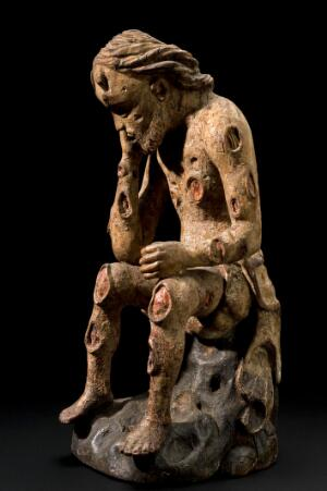 view Wooden figure of Job with an affliction of boils, possibly German, 1750-1850. Graduated black background, front 3/4 view.