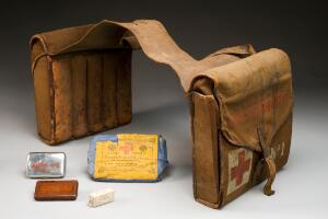 view Saddle-bag first aid kit, pair of canvas panniers linked by rubber band, containing dressings, tablets and ointments, many prepared by Burroughs Wellcome and Co., English, 1914-1918. Full view, some contents arranged around bags. Graduated brey background.