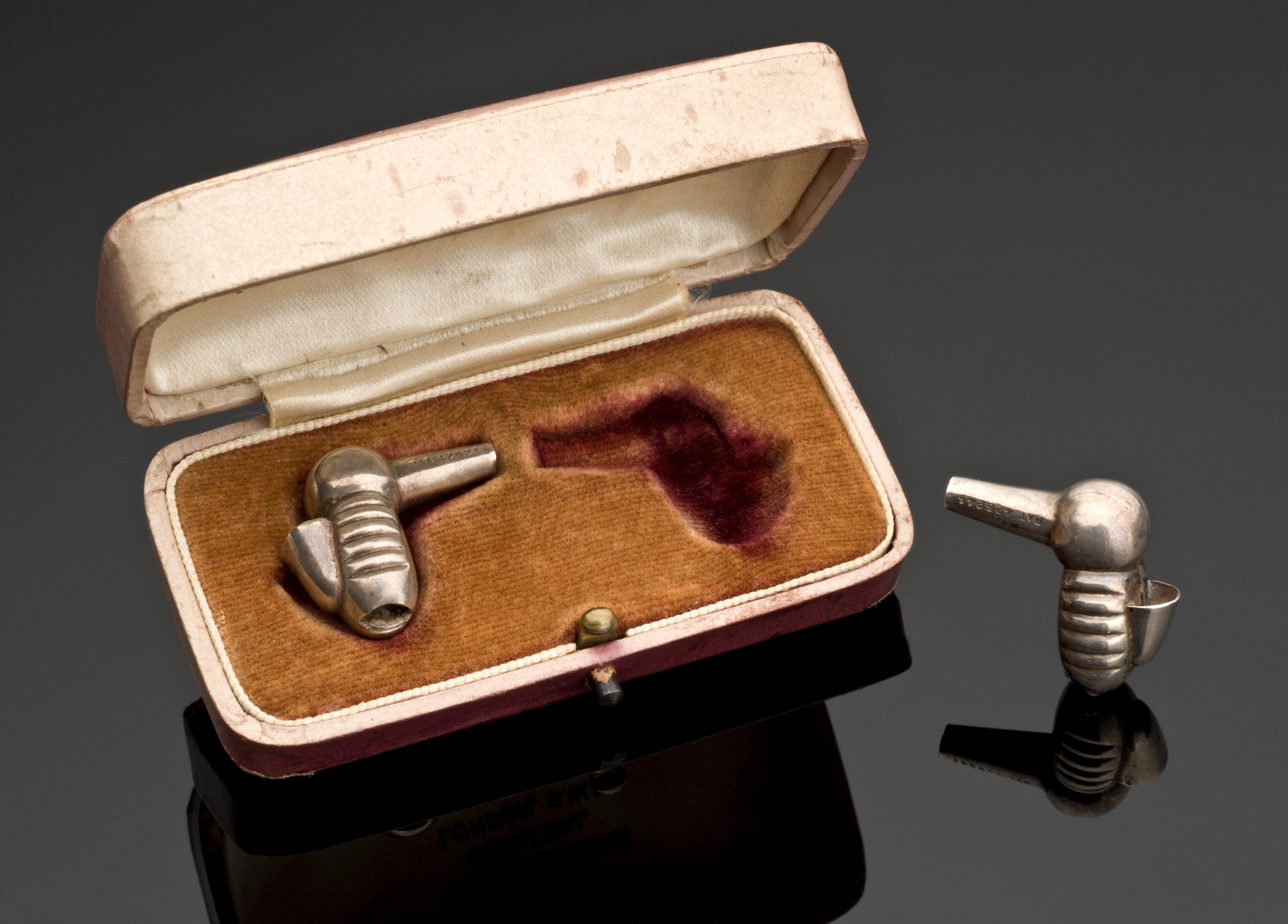 A small leather and fabric box containing two metal hearing aids shaped similarly to hummingbirds.