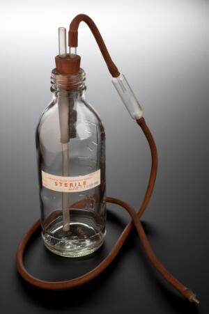 view Blood transfusion bottle, capped, with associated parts, Eng