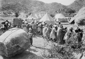 view Jebel Moya: natives hauling on rope, tents in the background