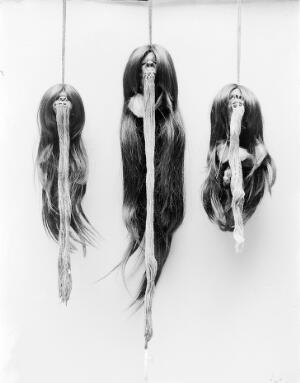 view Shrunken heads with strings from mouth.
