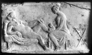 view Ancient Roman relief carving of a midwife attending a woman giving birth.