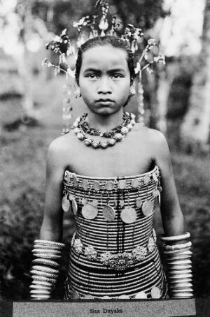 view Sea Dayaks, female figure wearing spiral corsets decorated with medals