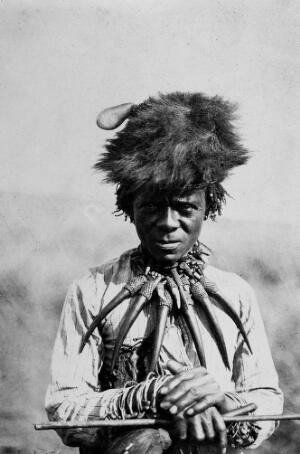 view Medicine Man wearing a necklet of horns and fur headress