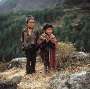 view Nepal; Sherpa children of the Khumbu, 1986. Two smiling children share an amusing moment in the village of Phakding (altitude 3000 metres). Their clothing highlights the poverty of some of the Sherpa families.