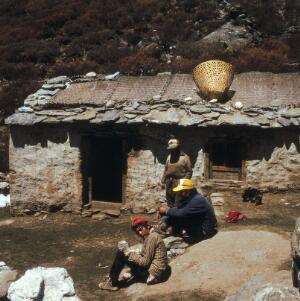 view Nepal; herdsmen of the Khumbu, 1986. Three herdsmen stop for refreshments at the Shomare Hotel. The sign above the door of this tea shop reads: 'Wel-come to Shomare Hotel', evidence that westerners pass the door en rout to the high mountains.
