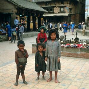 view Nepal; Kathmandu Valley, children of Bhaktapur, 1986. Three children stand in Durbar Square. The little boy has genu valgum (knock knees). In the mid-1980s, nearly half of all Nepalese children died before reaching the age of 5, and life expectancy at birth was 51 years for men and 50 years for women. Conditions associated with poor hygiene and sanitation, including gastrointestinal disorders, diarrhoea, and parasitic infestation, were common.