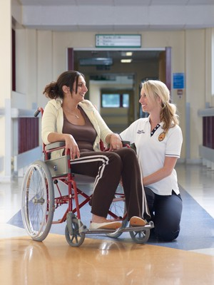 view Physiotherapist with patient in hospital corridor, UK.