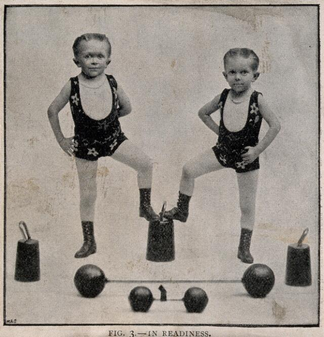 Two boys performing as strongmen. Reproduction of a photograph.