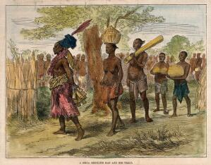 view A Mrua medicine man or shaman with his assistants, Central Africa. Coloured wood engraving after a sketch by Lieutenant Cameron.