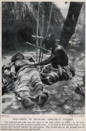 view An Ashluslay Indian medicine man examining a sick patient, South America. Halftone after a photograph E. Nordenskiöld.