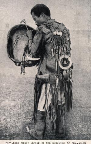 view A shaman with drum and in full costume. Process print.
