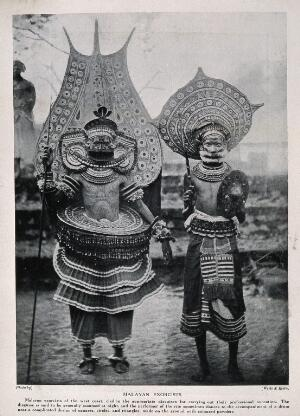 view Two Malayan exorcists dressed in elaborate ritual costume. Halftone after a photograph by Wiele & Klein.