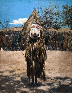 view An African shaman or medicine man dressed in ritual mask and costume. Coloured photograph.