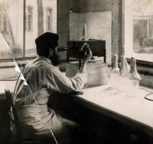 view A scientist controlling the titration of bacteria in the vaccine with an optical apparatus. Photograph, [ca. 1940].