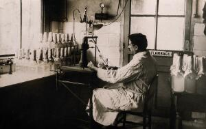 view A scientist using a device for the dilution of emulsions after microbial use. Photograph, [ca. 1940].