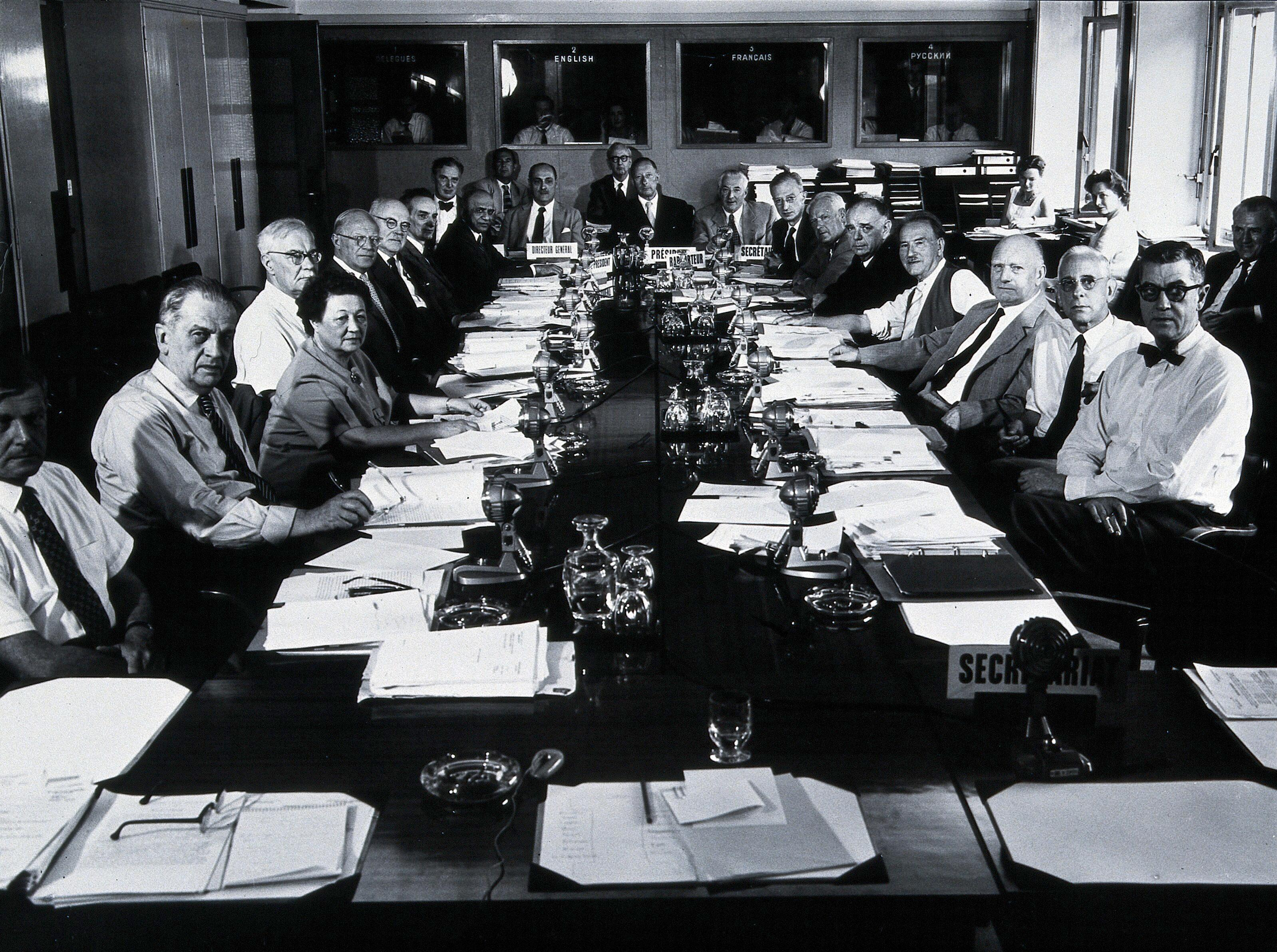 Black and white photograph of a group of people at a meeting in the 1960s